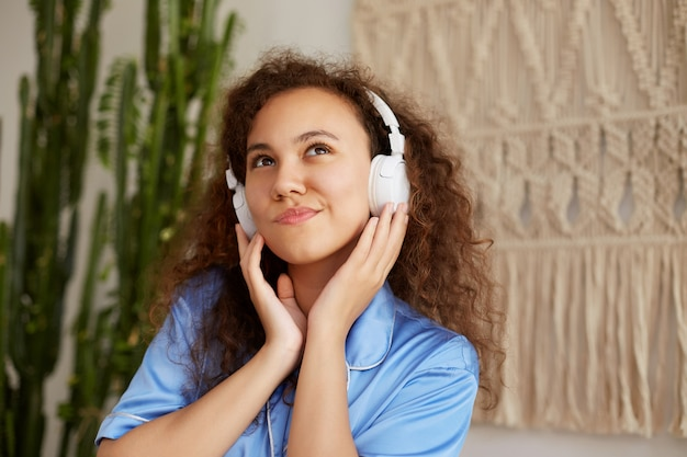 Photo de belle jeune femme afro-américaine frisée, écoute de la musique préférée dans les écouteurs, tient des écouteurs, regarde pensivement ailleurs.
