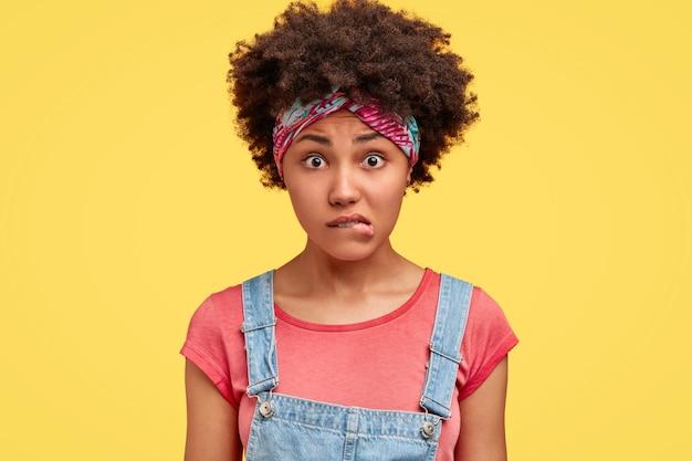 Photo de belle jeune femme afro-américaine nerveuse mord les lèvres, regarde avec stress et perplexité, porte une salopette en denim, pose seule contre un mur jaune. concept de réaction