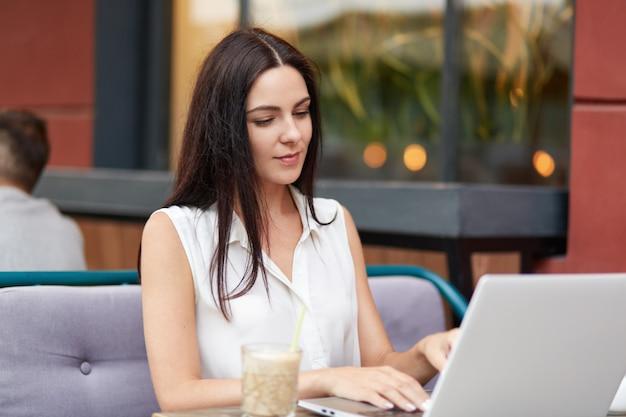 Photo d'une belle jeune femme aux cheveux noirs, informations sur les claviers sur un ordinateur portable, travaille à distance, boit un cocktail, passe du temps libre contre l'intérieur du café. concept technologique