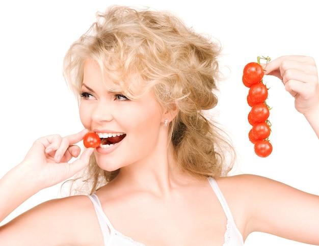 Photo de la belle jeune femme aux tomates mûres