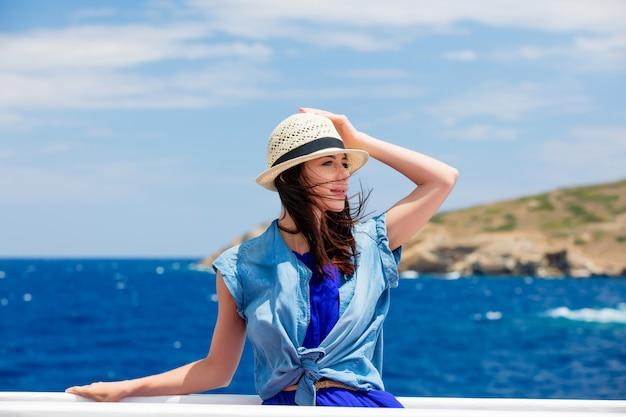 Photo de la belle jeune femme sur le bateau en face de la mer et du fond de l'île en grèce