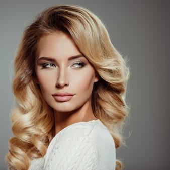 Photo d'une belle jeune femme blonde aux cheveux bouclés. gros plan visage sensuel attrayant de femme blanche. maquillage pour les yeux smokey.