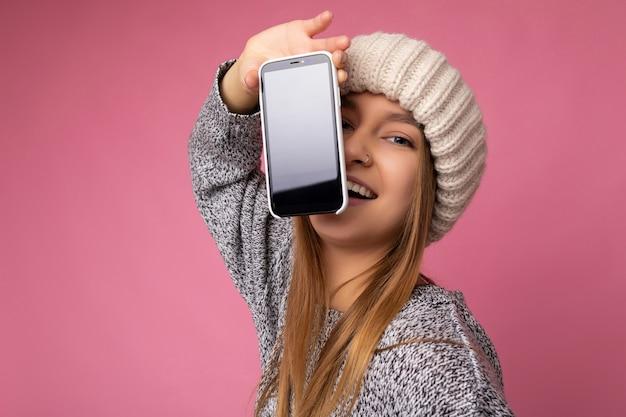 Photo de la belle jeune femme blonde portant un pull gris décontracté et un chapeau beige