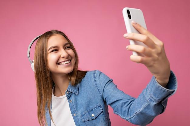 Photo D'une Belle Jeune Femme Blonde Souriante Et Heureuse Portant Une Chemise En Jean Bleu Et Un T-shirt Blanc Photo Premium