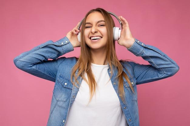 Photo d'une belle jeune femme blonde souriante et heureuse portant une chemise en jean bleu et un t-shirt blanc