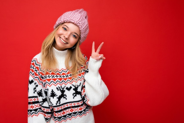 Photo de la belle jeune femme blonde souriante portant bonnet tricoté chaud et chandail chaud d'hiver debout isolé sur un mur rouge et montrant le geste de paix. copie espace