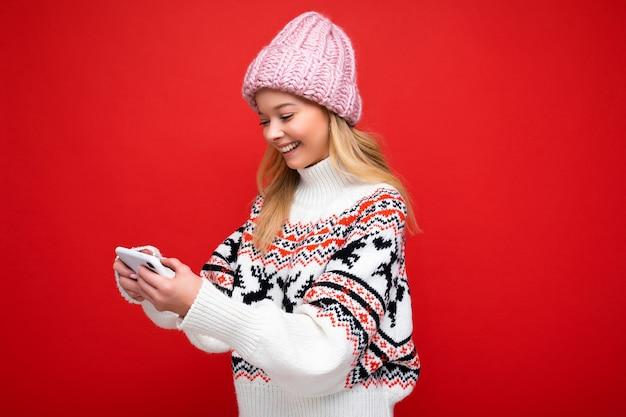 Photo d'une belle jeune femme blonde souriante portant un chapeau tricoté chaud et un pull chaud d'hiver, isolée sur fond rouge, jouant à des jeux via un smartphone en regardant l'affichage de l'appareil.