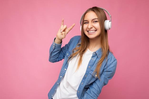 Photo d'une belle jeune femme blonde souriante et positive portant des casques bluetooth sans fil blancs