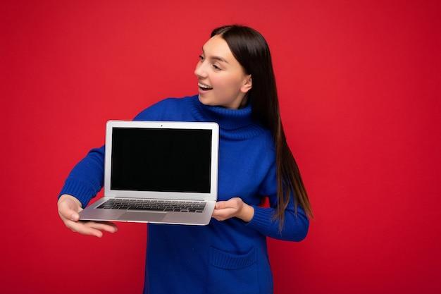 Photo d'une belle jeune femme brune assez heureuse tenant un ordinateur portable regardant sur le côté