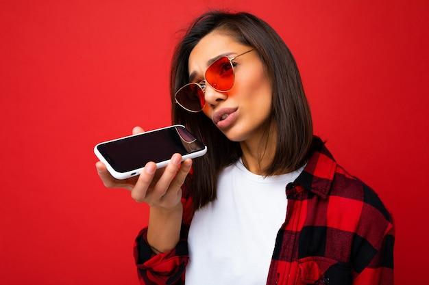 Photo d'une belle jeune femme brune en colère portant un t-shirt blanc élégant en chemise rouge et des lunettes de soleil rouges isolées sur fond rouge à l'aide d'un message vocal d'enregistrement de téléphone portable regardant sur le côté.