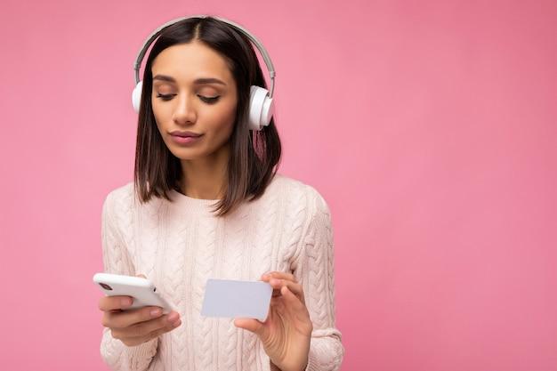 Photo d'une belle jeune femme brune concentrée portant un pull décontracté rose isolé sur un mur de fond rose portant des écouteurs sans fil bluetooth blancs et écoutant de la musique et utilisant un mobile