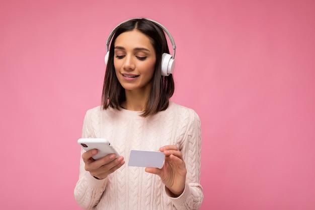Photo de belle jeune femme brune heureuse portant un pull décontracté rose isolé sur rose