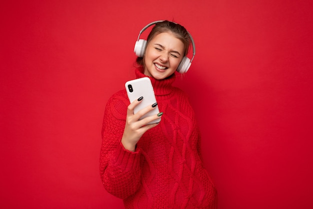 Photo d'une belle jeune femme brune heureuse portant un pull rouge isolé sur un mur de fond rouge tenant et utilisant un téléphone portable et portant des écouteurs bluetooth s'amusant.
