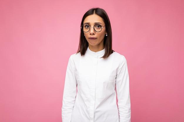 Photo de belle jeune femme brune insatisfaite portant des vêtements décontractés et des lunettes optiques élégantes