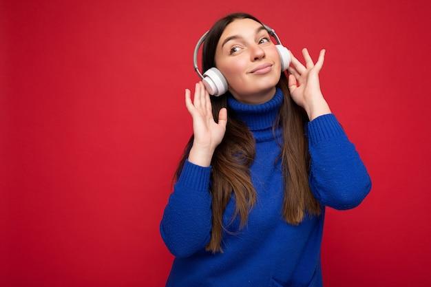 Photo de belle jeune femme brune portant un pull bleu isolé sur fond rouge