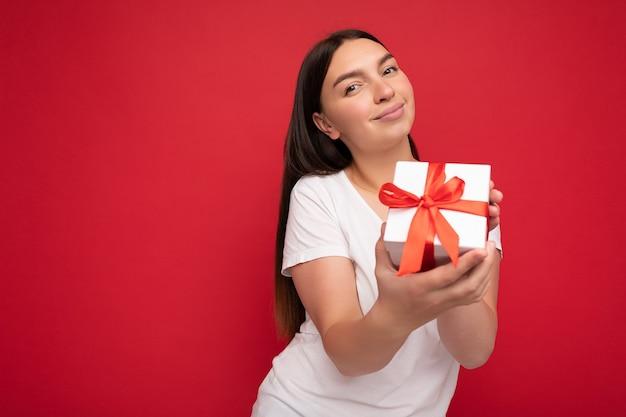 Photo d'une belle jeune femme brune positive isolée sur un mur de fond rouge portant un t-shirt décontracté blanc pour une maquette tenant une boîte-cadeau blanche avec un ruban rouge et regardant la caméra. espace libre