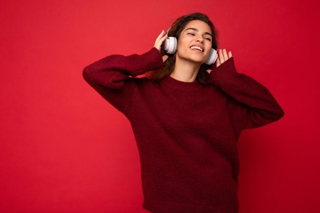 Photo d'une belle jeune femme brune souriante et frisée portant un pull rouge foncé isolé sur