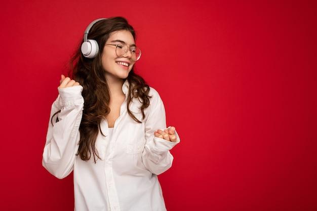Photo de belle jeune femme brune souriante et heureuse portant une chemise blanche et des lunettes optiques