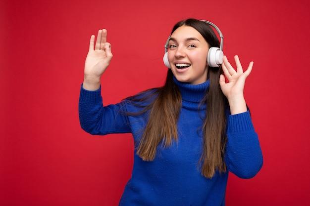 Photo d'une belle jeune femme brune souriante et heureuse portant un pull bleu isolé sur un mur de fond rouge portant des écouteurs bluetooth blancs, écoutant de la musique cool et dansant en regardant la caméra.