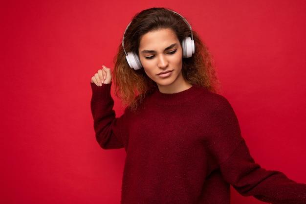 Photo de belle jeune femme brune souriante heureuse portant un pull rouge foncé isolé sur