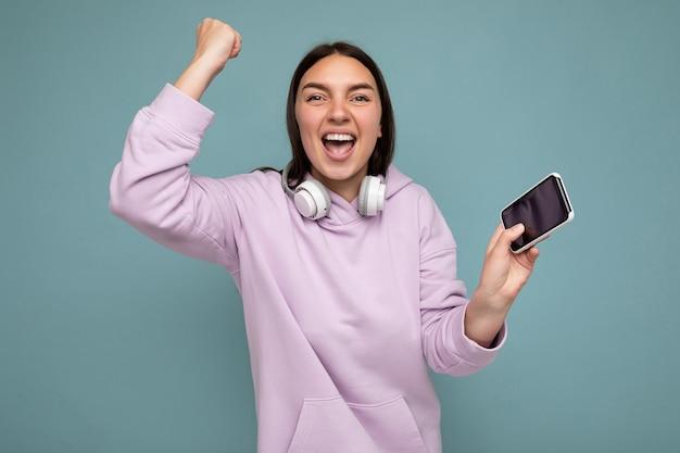 Photo de belle jeune femme brune souriante et positive portant un sweat à capuche violet isolé sur bleu