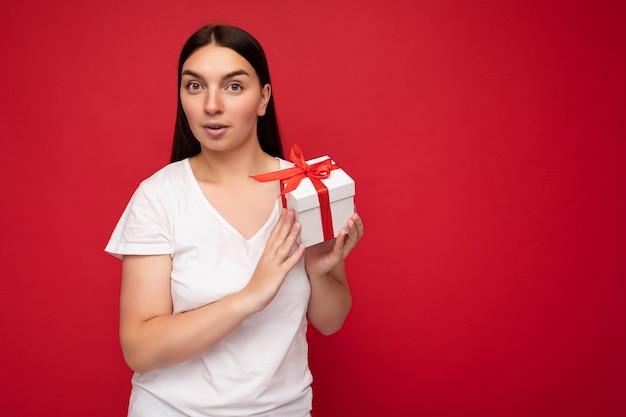 Photo de belle jeune femme brune surprise positive isolée sur mur rouge portant