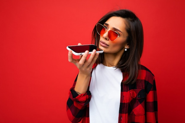 Photo d'une belle jeune femme brune triste portant un t-shirt blanc élégant avec une chemise rouge et des lunettes de soleil rouges isolées sur fond rouge à l'aide d'un message vocal d'enregistrement de téléphone portable regardant sur le côté.