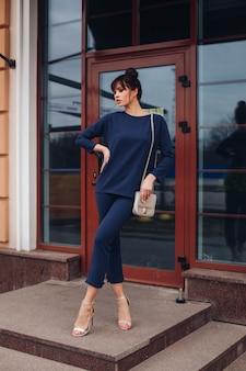 Photo d'une belle jeune femme caucasienne aux cheveux noirs en blouse bleu foncé et pantalon bleu foncé, chaussures blanches avec sac blanc