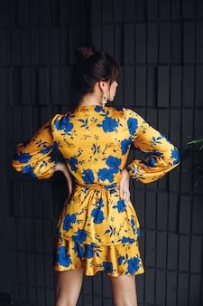 Photo d'une belle jeune femme caucasienne aux cheveux noirs en robe jaune et bleue, des chaussures dorées montrent différentes poses pour l'appareil photo