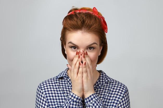 Photo de belle jeune femme émotionnelle dans des vêtements à la mode couvrant la bouche, étonnée par un cadeau inattendu de petit ami
