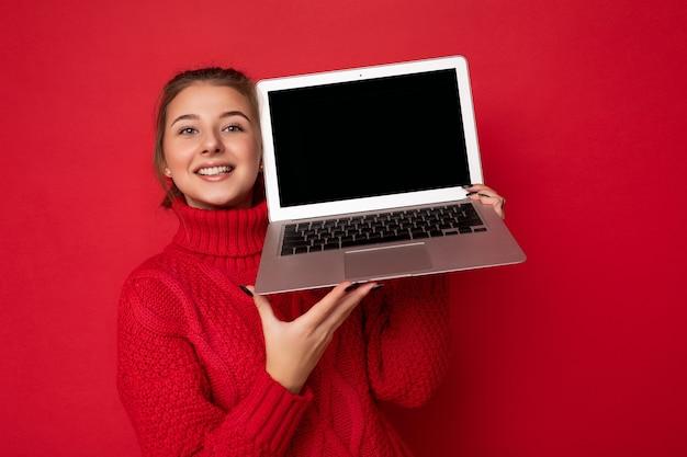 Photo d'une belle jeune femme heureuse et satisfaite tenant un ordinateur portable regardant la caméra en portant du rouge