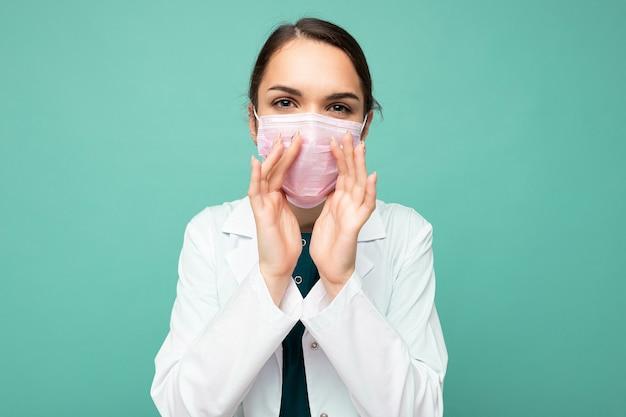 Photo de la belle jeune femme médecin en blouse blanche et masque médical debout isolé sur bleu