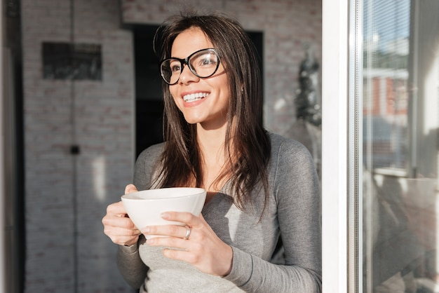 Photo de belle jeune femme portant des lunettes buvant du café à l'intérieur. regarder de côté.