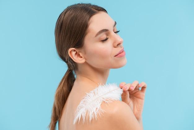 Photo de la belle jeune femme posant plume de tenue isolée.