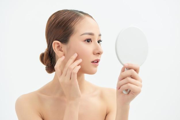 Photo d'une belle jeune femme se regardant dans un petit miroir sur fond blanc isolé.
