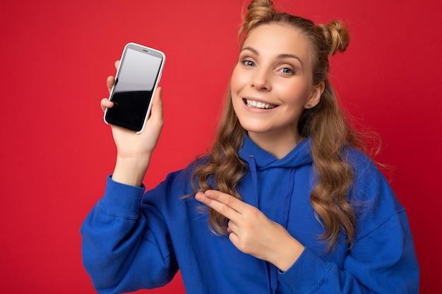 Photo d'une belle jeune femme souriante belle portant une tenue élégante décontractée, isolée sur fond avec espace de copie tenant un smartphone montrant le téléphone à la main avec un écran vide pour