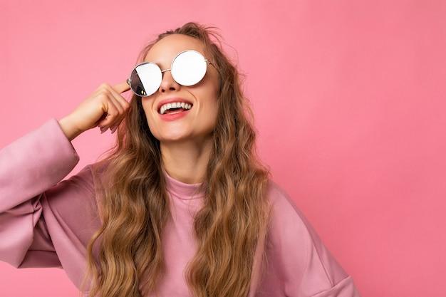 Photo d'une belle jeune femme souriante et bouclée blonde foncée isolée sur un mur de fond rose
