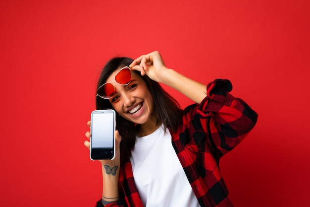 Photo d'une belle jeune femme souriante et heureuse portant un t-shirt blanc élégant et décontracté avec une chemise rouge et des lunettes de soleil rouges isolées sur fond rouge avec un espace de copie tenant un smartphone showi
