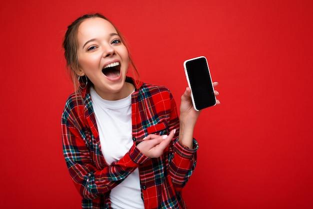 Photo de la belle jeune femme souriante ravie à la recherche de vêtements élégants décontractés debout
