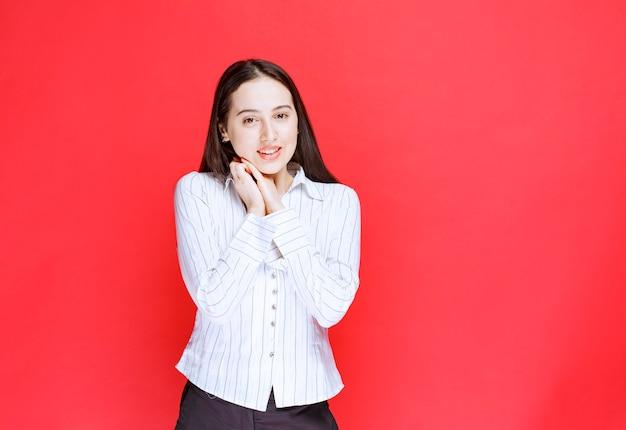 Photo de belle jeune femme en tenue formelle se présentant à la caméra.