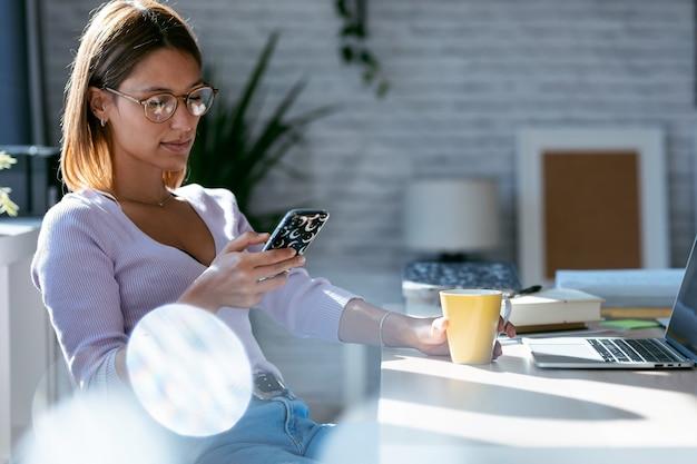 Photo d'une belle jeune femme utilisant son téléphone intelligent tout en buvant du café au bureau à la maison.