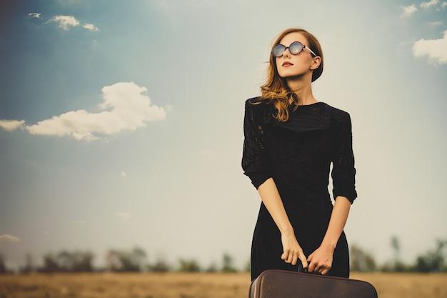 Photo de belle jeune femme avec valise sur le magnifique champ et ciel