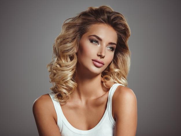 Photo d'une belle jeune fille blonde aux cheveux bouclés. gros plan visage sensuel attrayant de femme blanche aux cheveux longs. maquillage pour les yeux smokey.