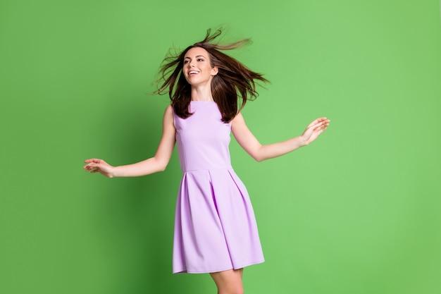 Photo de belle jolie dame adorable modèle look espace vide mains mouche légère aérée vent soufflant cheveux volume shampooing effet revitalisant porter robe violette fond de couleur vert pastel isolé