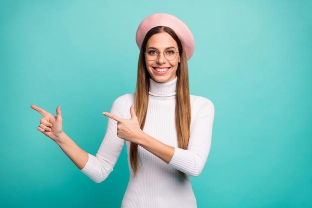 Photo de belle jolie dame doigts directs vente publicité bannière espace vide incroyable prix bas offre porter des spécifications béret rose casquette col roulé blanc isolé fond de couleur sarcelle