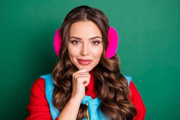 Photo de belle jolie jeune femme doigt menton regard confiant pensant meilleure occasion passer l'hiver porter des cache-oreilles roses gilet bleu pull rouge isolé fond de couleur verte