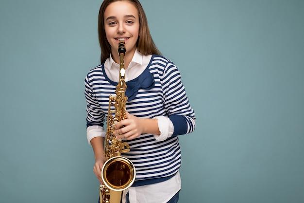 Photo d'une belle petite dame brune souriante et heureuse portant une chemise à manches longues à rayures élégantes