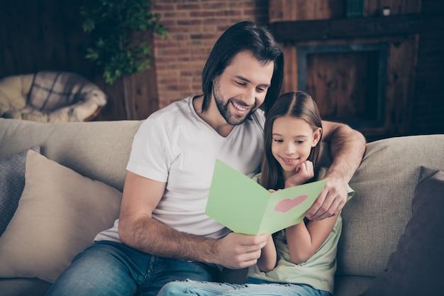 Photo de belle petite fille adorable et beau jeune papa assis sur un canapé confortable
