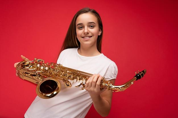 Photo d'une belle petite fille brune souriante et positive portant un t-shirt blanc pour une maquette debout isolée sur un mur de fond rouge tenant un saxophone regardant la caméra.