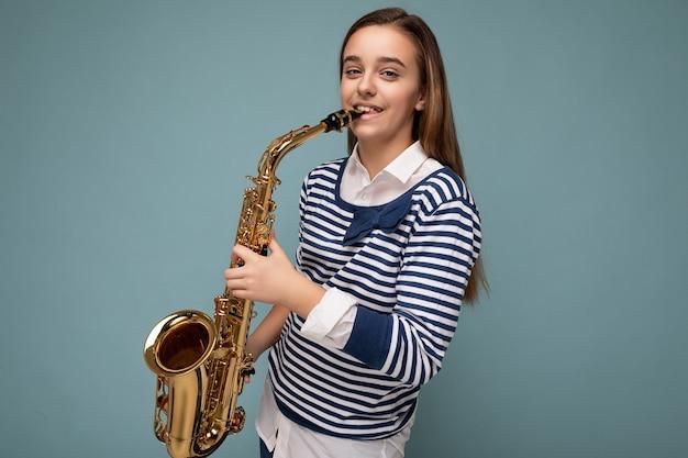 Photo d'une belle petite fille brune souriante et souriante portant une chemise à manches longues rayée, isolée sur un mur de fond bleu jouant du saxophone en regardant la caméra.